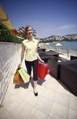 Woman walking on promenade with shopping bags