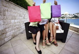 Three women hiding behind shopping bags