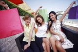 Three women with shopping bags posing