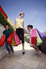 Mother and two children jumping with shopping bags *** Local Caption *** All ages enjoying a day of shopping in a modern urban environment