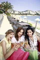 Three women with shopping bags and wine posing