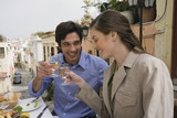 Couple toasting at a table with Greek food