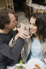 Couple drinking wine with linked arms