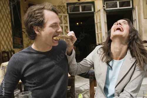 Woman feeding man a lamb chop