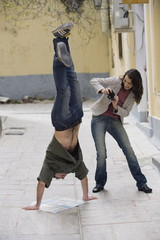 Woman photographing man doing handstand