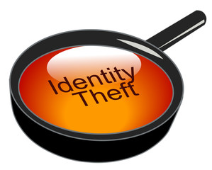 magnifying glass over top of identity theft ..