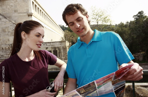 Couple at archaeological site reading map