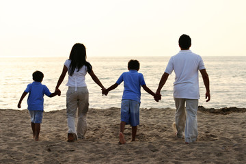 Family Holding Hands at the Beach Together