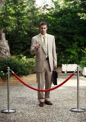 Businessman in garden behind barrier