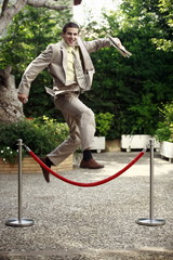 Businessman in garden jumping over barrier