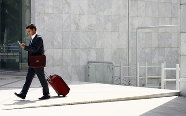 Businessman walking with a suitcase and cell phone