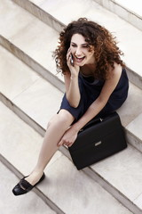 Businesswoman on cell phone sitting with briefcase