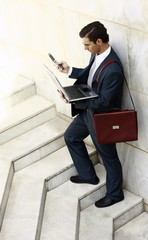 Businessman holding laptop and cell phone
