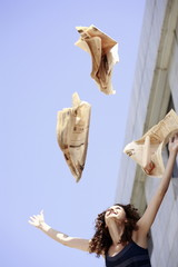 Happy businesswoman throwing newspaper in the air