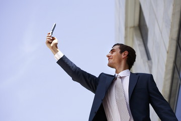 Businessman holding cell phone to get a signal