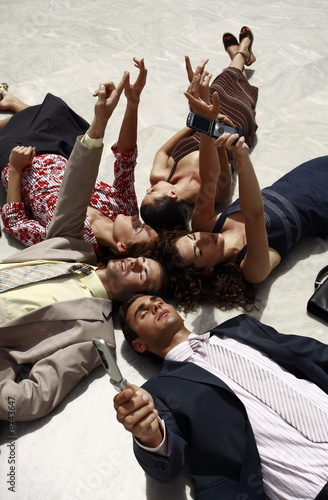Business people lying on the ground pointing