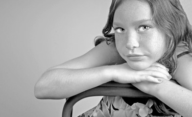 Young girl leaning on chair