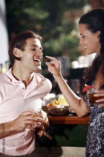 Woman feeding man in a bar