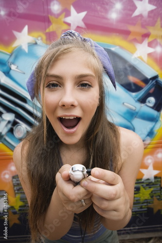 Female teenager with mp3 player in front of graffiti