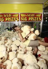 Female teenager among teddy bears in arcade