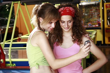 Female teenagers taking picture of themselves with cell phone camera