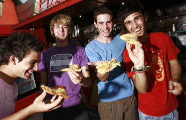 Male teenagers hanging out;eating pizza