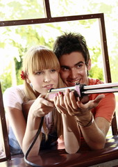 Teenage couple at shooting game in amusement park