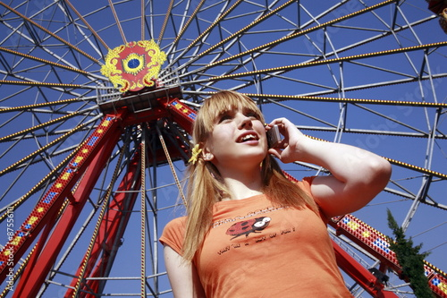 Female teenager on cell phone at Ferris wheel in amusement park