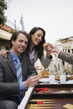 Business couple at taverna with backgammon;appetizers;and ouzo