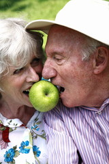 Senior couple both biting apple
