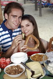 Young adult couple at breakfast holding sesame bread ring and melon