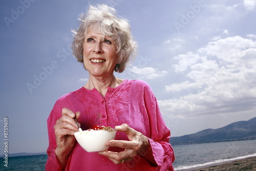 Female senior eating yogurt and fruit on the beach