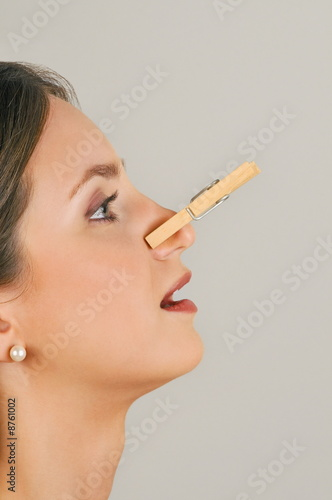 Female young adult with clothes pin on nose
