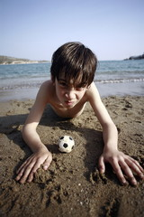 Boy with small soccer ball on beach