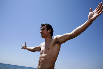 Male young adult on beach spreading arms