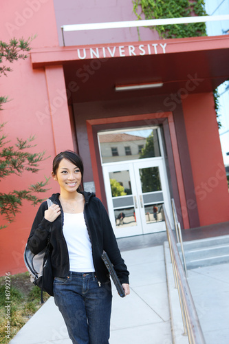 A pretty young asian woman at university walking to class