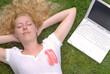 Frau liegt mit Laptop auf der Wiese