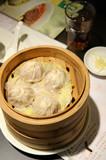 Shanghai soup dumplings served in bamboo steamer basket poster
