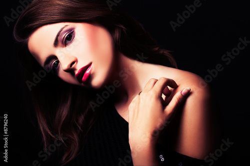 brunette girl posing in studio on dark background