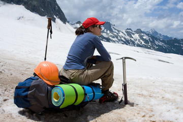 alpinist woman sitting on her backpack in snowy mountains