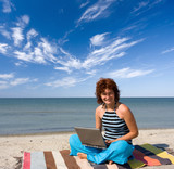 girl sitting with laptop on the sea coast