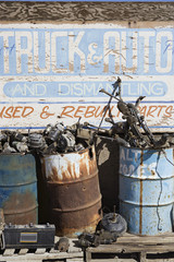 Rusty sign and barrels in junkyard