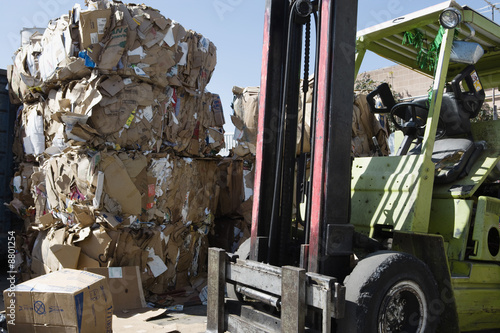 Stacks of cardboard boxes in recycling centre and forklift truck