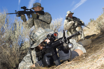 Soldiers aiming machine guns