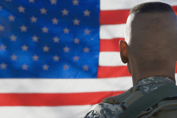 US Army soldier looking at flag, back view