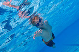 Boy swimming underwater, sunny outdoor conditions poster
