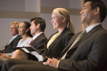 Five businesspeople smiling in presentation room with clipboards