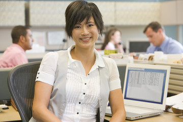 Businesswoman in cubicle smiling