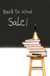 School books on stool with chalkboard