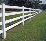 A long white fence on a mountain ranch. poster